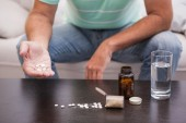Man with his medicine laid out on coffee table — Stock Photo