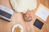 Man lying on floor surrounded by various objects — Stock Photo