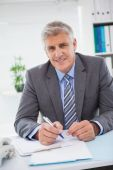Smiling businessman writing on clipboard — Stock Photo