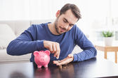 Young man putting coins in piggy bank — Foto Stock