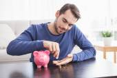 Young man putting coins in piggy bank — Stockfoto
