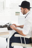 Hipster businessman using a typewriter — Stock Photo