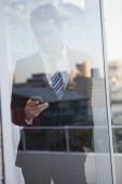 Businessman sending a text seen through window — Stock Photo