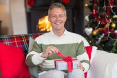 Smiling man opening a gift on christmas day — Stockfoto