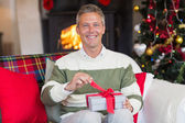 Smiling man opening a gift on christmas day — 图库照片
