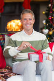 Smiling man opening a gift on christmas day — Foto Stock