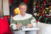 Man opening a gift on the couch at christmas — Foto Stock