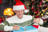 Smiling man in santa hat opening a gift — Foto Stock