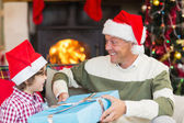 Son giving father a christmas gift on the couch — Foto de Stock