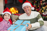 Son giving father a christmas gift on the couch — Foto Stock