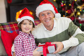 Son offering father a christmas gift on the couch — Stockfoto