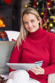 Festive blonde woman using her credit card and tablet pc — ストック写真