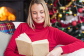 Pretty blonde reading book at christmas time — Stockfoto