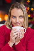 Pretty blonde relaxing on sofa at christmas — Stock Photo