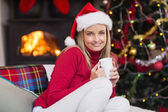 Smiling blonde holding a mug of hot chocolate at christmas — 图库照片