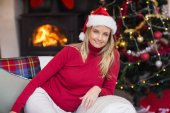 Happy blonde relaxing on the couch at christmas — Stockfoto