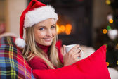 Smiling blonde wearing santa hat while holding a mug  — Foto Stock