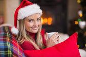 Smiling blonde wearing santa hat while holding a mug  — 图库照片