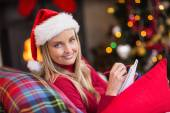 Blonde sitting on the couch writing her christmas list — Stock Photo