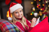 Blonde sitting on the couch writing her christmas list — 图库照片
