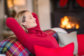 Smiling blonde relaxing on the couch at christmas — Stock Photo