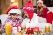 Festive little girl opening a gift with brother — Stock Photo