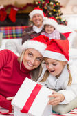 Surprised mother and daughter opening a christmas gift — Stockfoto