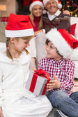 Festive little siblings opening a gift in front of their parents — Stockfoto