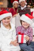 Festive little siblings opening a gift in front of their parents — Стоковое фото
