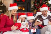Festive shocked family exchanging gifts — Stock Photo