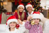 Cute little siblings wearing santa hat holding baubles — Stockfoto