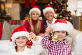 Cute little siblings wearing santa hat holding baubles — Stok fotoğraf