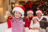 Son wearing santa hat holding baubles in front of his family — Stok fotoğraf