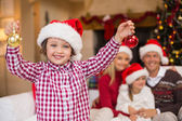 Son wearing santa hat holding baubles in front of his family — Stockfoto