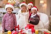 Portrait of a festive family in santa hat — Stock Photo