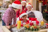 Smiling family at christmas time with lots of presents — Stock Photo