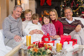 Multi generation family smiling at camera during christmas — Stock Photo