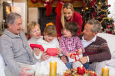 Multi generation family opening presents on sofa — Stock Photo