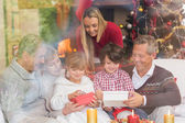 Multi generation family opening presents on sofa — Stock Photo