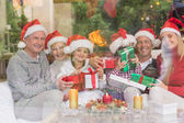 Multi generation family holding a lot of presents on sofa — Stock Photo