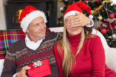 Man covering partner eyes and offering a gift to her — Stock Photo