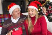 Loving couple in santa hat with gift — Stock Photo