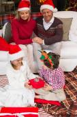 Parents sitting on couch looking children opening their gifts — Stockfoto