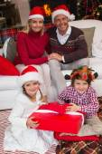 Family in santa hats celebrating christmas — Stock fotografie