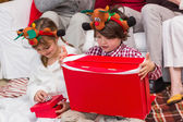 Festive sibling opening a gift — Stock Photo