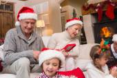 Happy family opening christmas gifts together — Foto de Stock