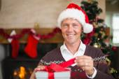 Smiling handsome man in santa hat opening a gift — Stock Photo