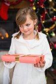 Portrait d'une petite fille souriante tenant un cadeau enveloppé — Photo
