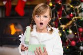 Shocked little girl opening a gift — Stock Photo