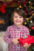 Festive little boy holding a gift — Стоковое фото